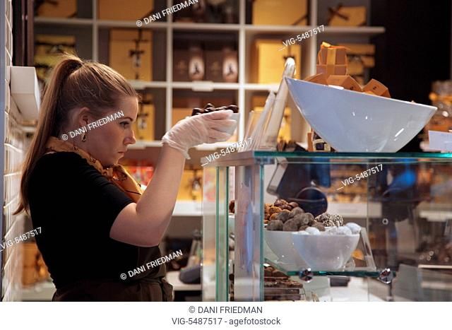 An employee at the Godiva chocolate shop removes fresh pralines from the showcase in Brussels, Bruxelles, Belgium, Europe