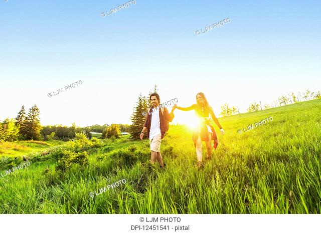 Young couple walking together in a city park at sunset; Edmonton, Alberta, Canada