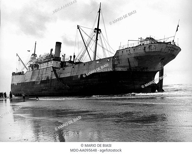 A merchant ship has run aground. A merchant ship has run aground on the coast, owing to a heavy storm. Netherlands, February 1953