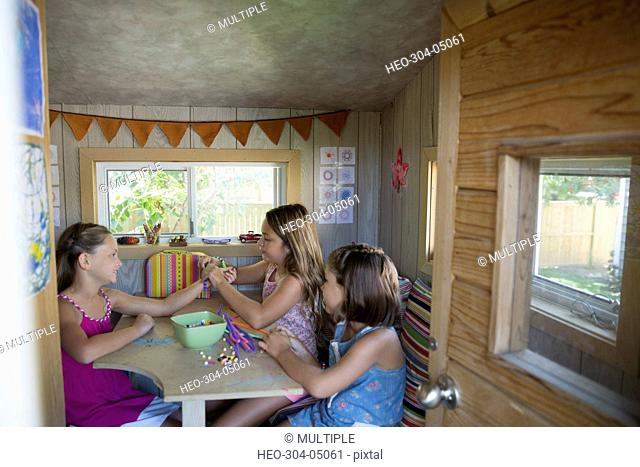 Girls making jewelry in treehouse