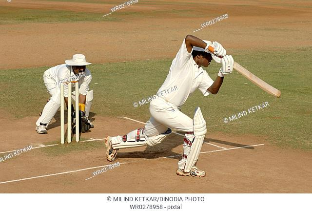 Indian left handed batsman in action playing cover drive shot in cricket match MR705I