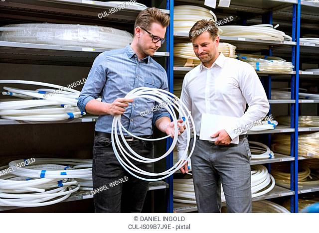 Two male managers inspecting cable product in factory warehouse