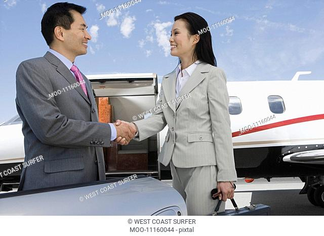 Mid-adult businesswoman and mid-adult businessman shaking hands in front of private plane
