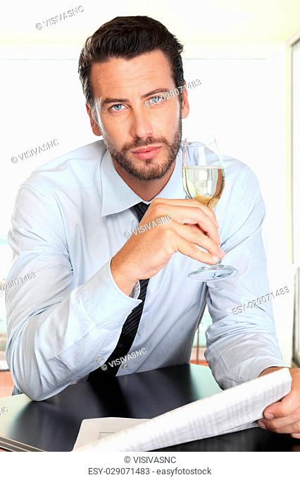 handsome man drinking a glass of sparkling wine white, sitting at the bar with newspaper