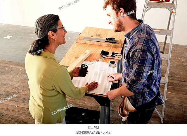 Carpenter looking at blueprint with client