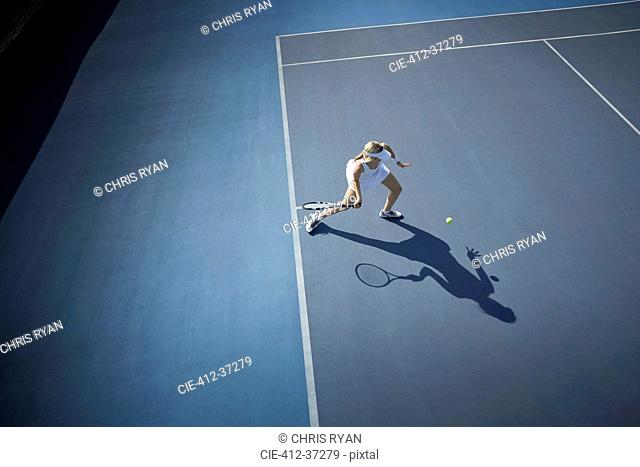 Overhead view young female tennis player playing tennis, hitting the ball on sunny blue tennis court