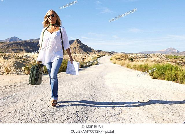 Woman walking alone on dusty road