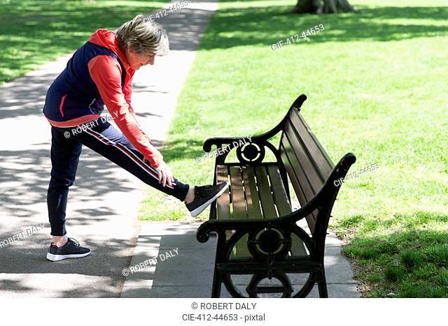 Active senior woman stretching leg on park bench