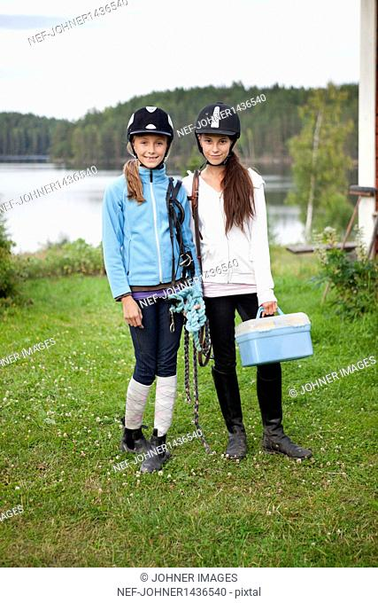 Two girls in jockey clothing standing on lawn