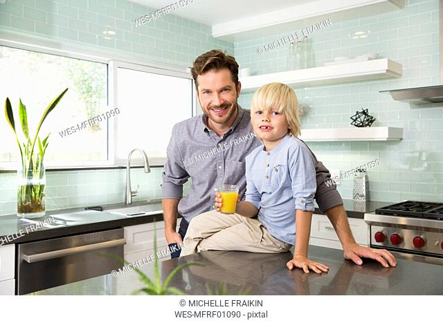Portrait of boy with father in kitchen holding glass of orange juice