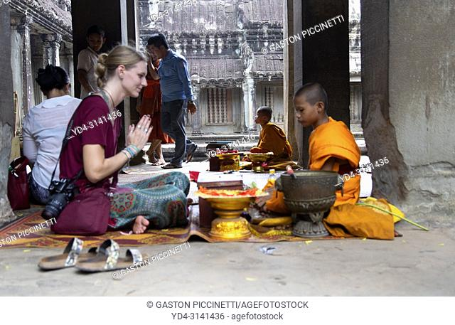 Buddhist monk blessing a woman in Angkor Wat Temple, Angkor Temple Complex, Siem Reap Province, Cambodia, Asia, UNESCO. It was originally constructed as a Hindu...