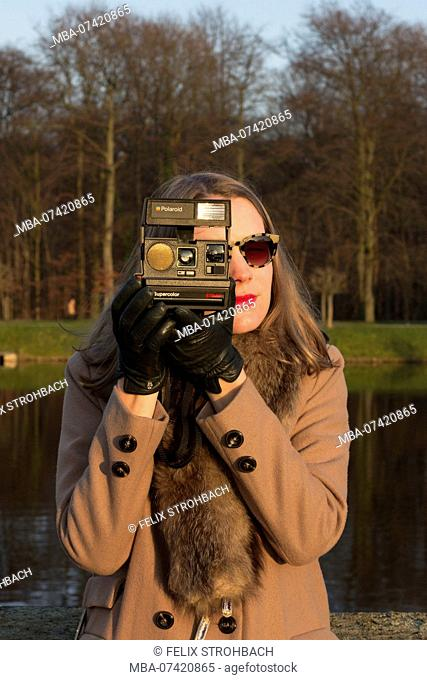 Young woman photographing with an instant camera