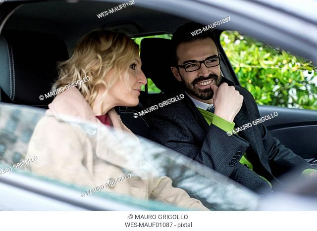 Smiling businessman and businesswoman in car