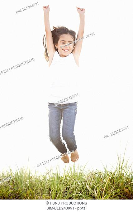 Mixed Race girl jumping for joy in grass