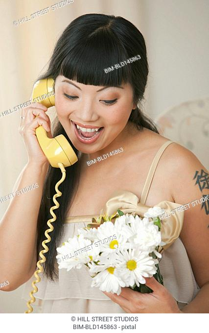 Elegant Asian woman holding bouquet of flowers and talking on telephone