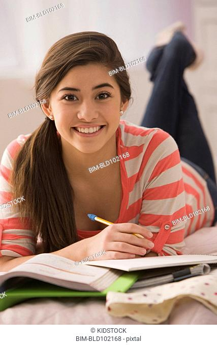 Mixed race girl laying on bed doing homework