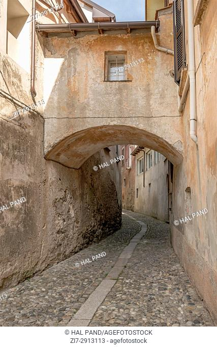 arched covered bridge between houses in historical village, shot on bright summer day at Miasino, Novara, Cusio, Italy
