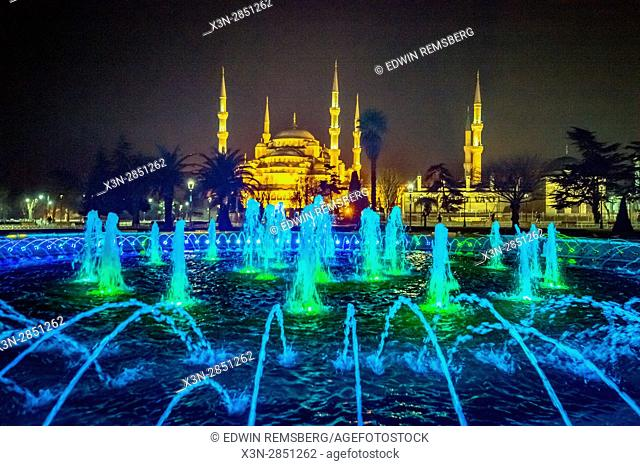 Colorful lights shine through a large fountain in front of the Sultan Ahmed, or Blue Mosque, in Sultanahmet square, Istanbul, Turkey