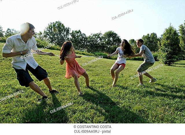 Group of young adults playing tug of war