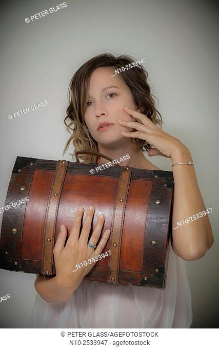 Young woman holding a wooden case