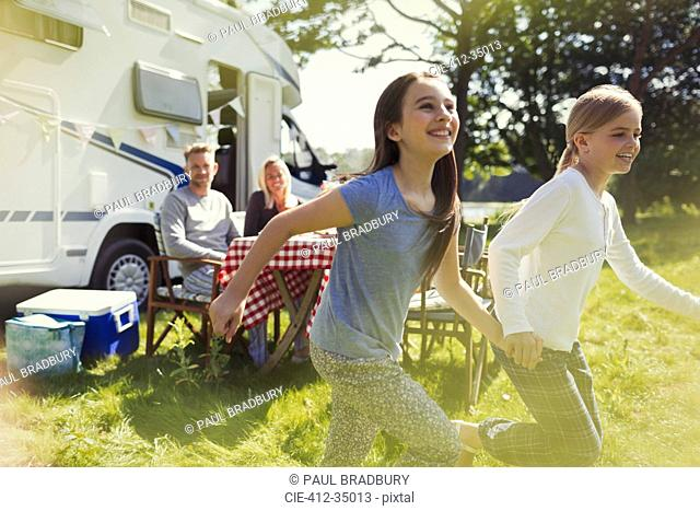 Playful sisters running and holding hands outside sunny motor home