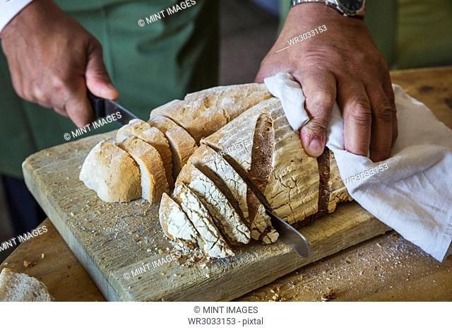 Close up high angle view of person slicing freshly baked loaf of bread
