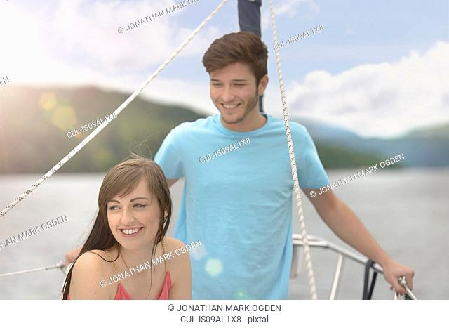 Young couple on bow of yacht sailing on lake under bright sunlight