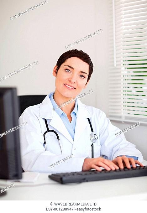 Portrait of a doctor typing with her computer in her office