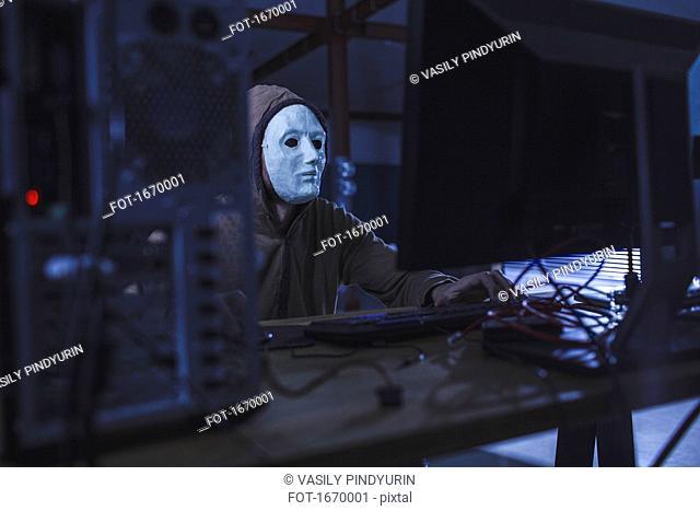 Man wearing mask and hood using computer at table