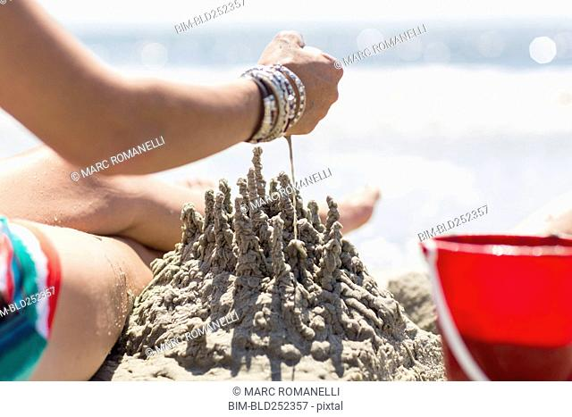 Caucasian woman playing with sand castle at beach