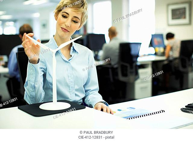 Businesswoman examining toy wind turbine in office