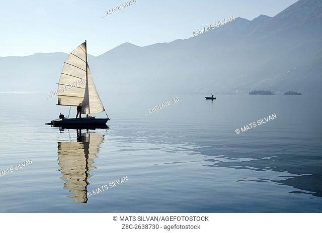 Sailing boat reflected on alpine lake Maggiore with Brissago islands and mountain in Ascona, Switzerland