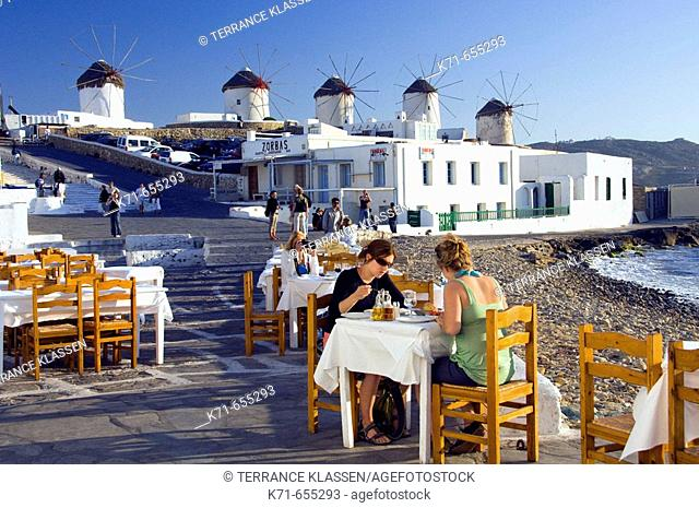 The windmills of Hora overlook the restaurants and bars of Little Venice on the Greek Island of Mykonos, Greece