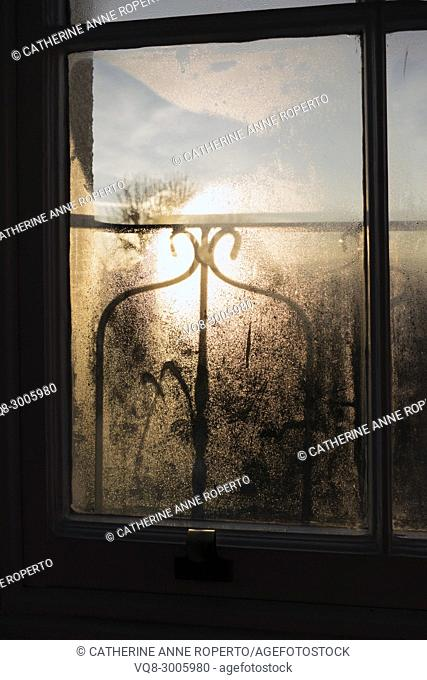Sunrise and shadows through a misty window pane and decorative ironwork balcony over the harbour, Hotwells, Bristol