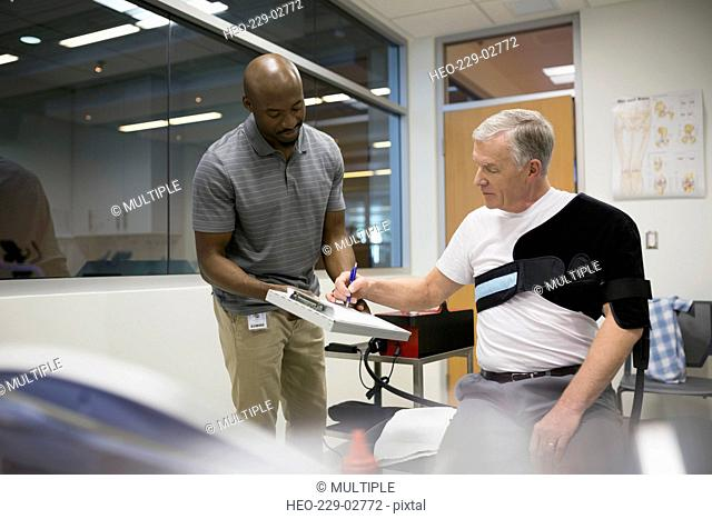 Patient in shoulder wrap signing waiver physical therapist