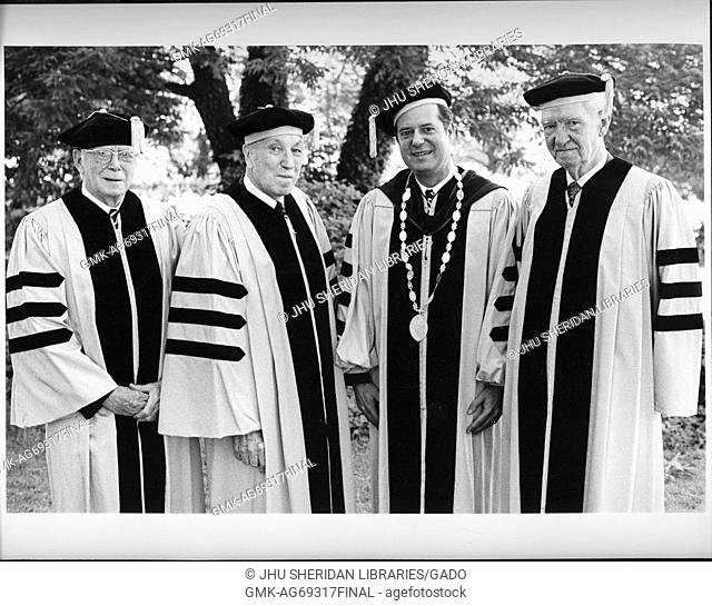 Three-quarter portrait of three Johns Hopkins professors and the president, standing in robes and caps on commencement day, in front of a tree