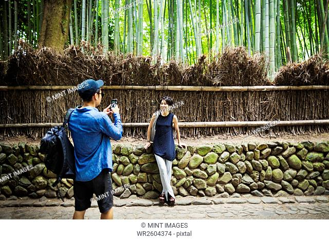A man taking a photograph of a woman by a fence around woodland