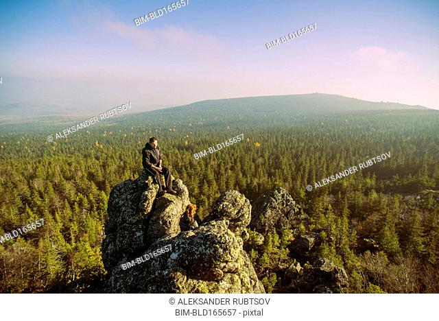 Caucasian hikers admiring view from remote rock formation