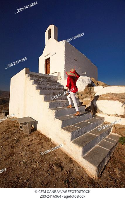 Woman climbing up to the chapel at the top of the hill in Chora, Ios, Cyclades Islands, Greek Islands, Greece, Europe