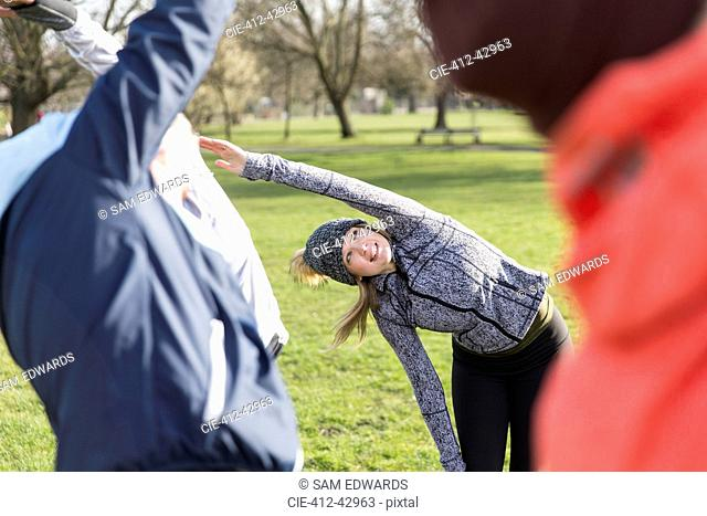 Woman exercising, stretching in park