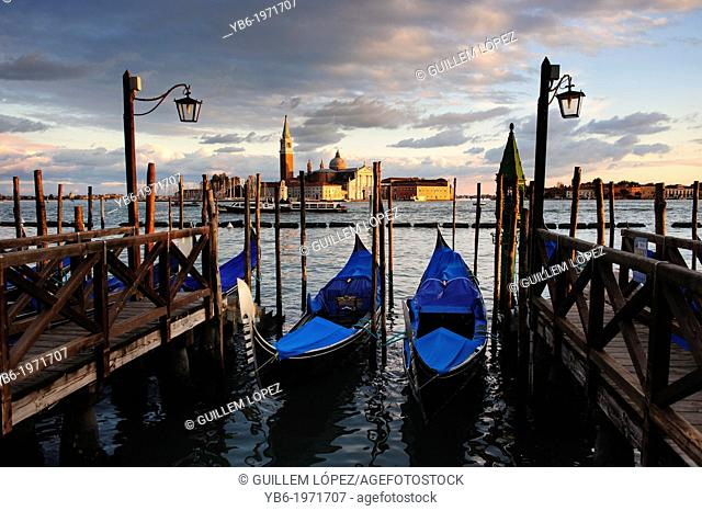 Gondolas moored at Venice waterfront with San Giorgio Maggiore in the background, Italy