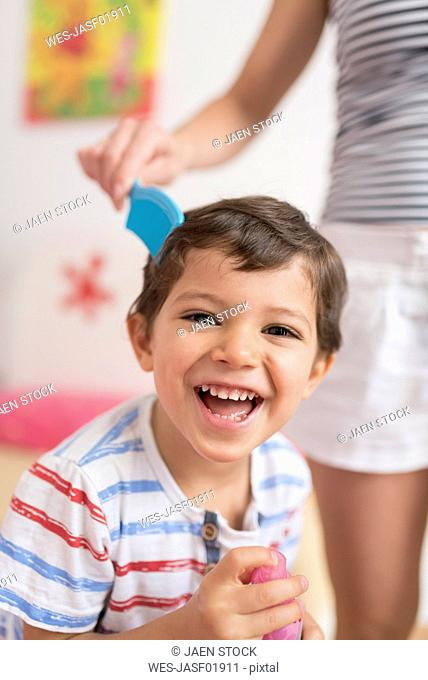 Portrait of happy little boy combed by his mother