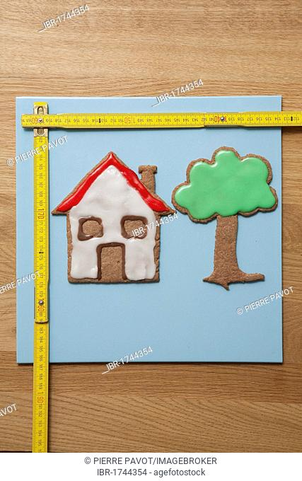 House and tree biscuits with a measuring stick, symbolic image for home construction