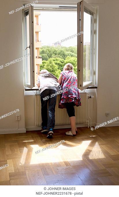 Boy and girl looking through window