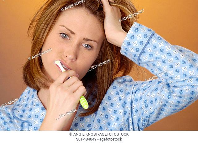 Young woman in blue patterned flannel pajamas, brushing her teeth, holding her head and looking very tired