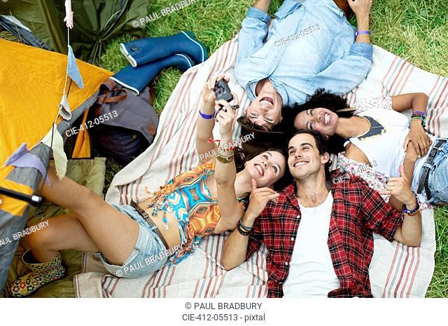 Friends taking self-portrait on blanket outside tent at music festival