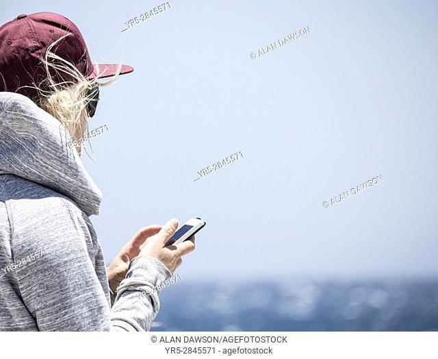 Female surfer with mobile phone on beach in Spain