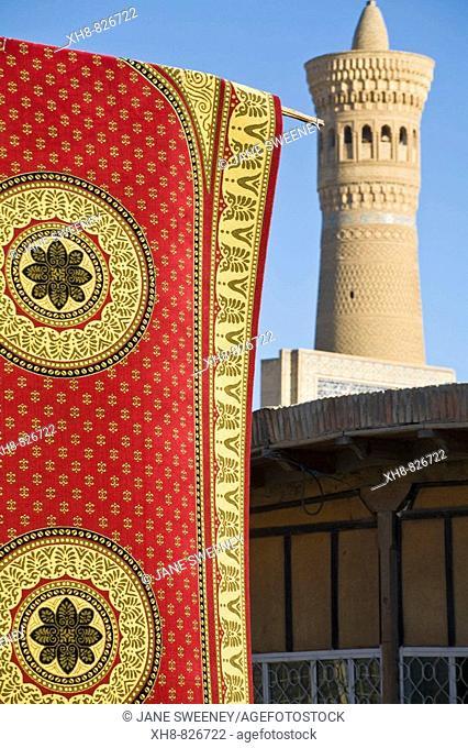 Carpet hanging up at market in front of Kalyan Mosque minaret, Bukhara, Uzbekistan