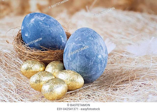 A background with beautiful Easter eggs on straw. Selective focus