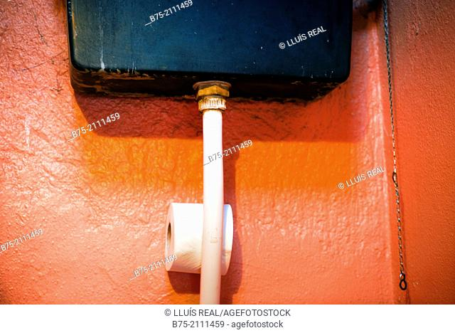 Red wall with a toilet tank and a roll of toilet paper. England, UK, Europe